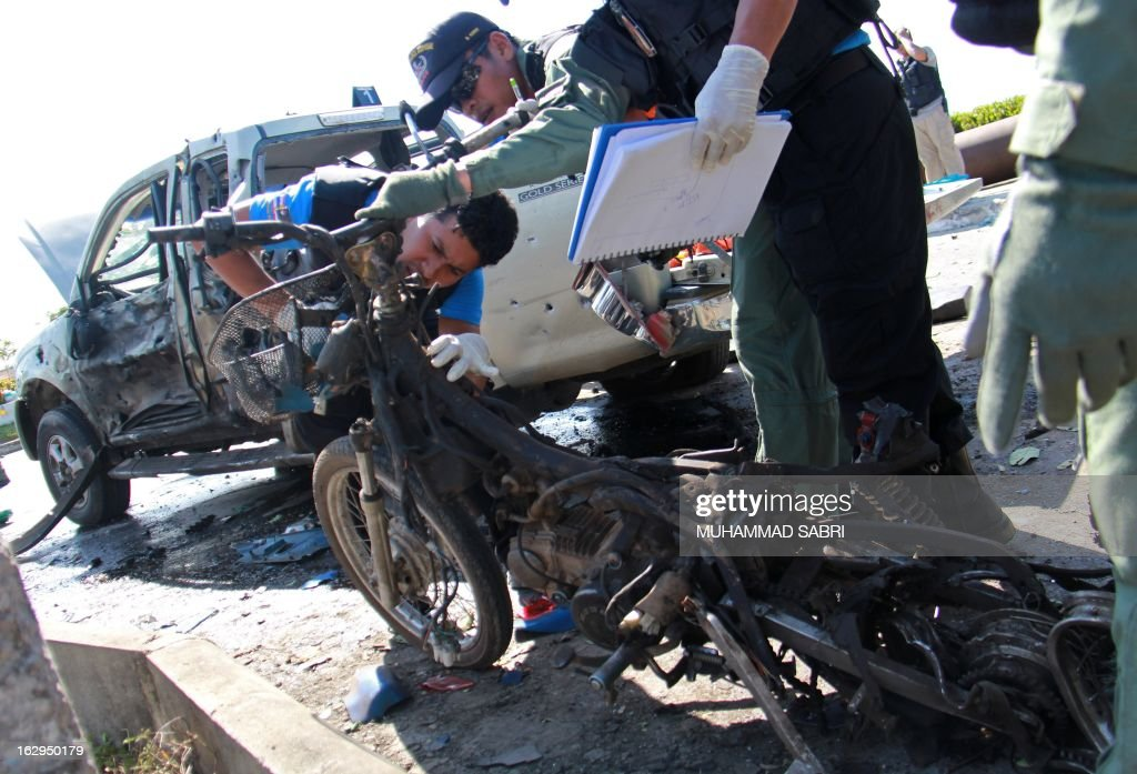 Members of a Thai bomb squad unit inspect the wreckage of a motorcycle caused from bomb attacks by militants in Yala province on March 2, 2013. Motorcycle bomb killed at least one ranger and injured nine others including two villagers in restive southern Thailand, army spokesman said. AFP PHOTO/MUHAMMAD SABRI