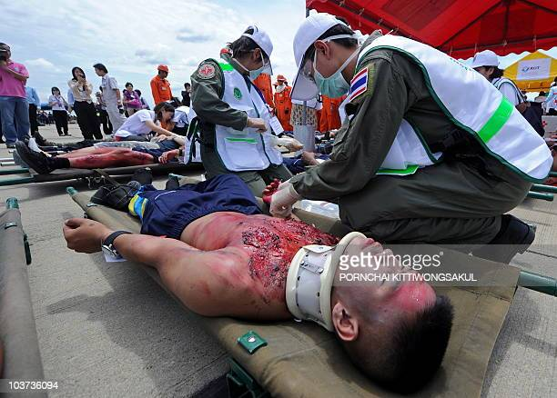 Members of a Thai medical team give 'firstaid' to injured passengers during a 'fullscale emergency' exercise at Don Muang airport in Bangkok on...