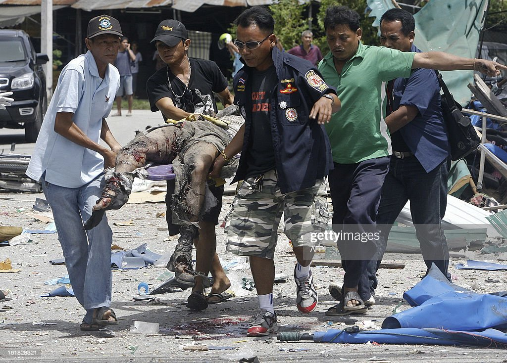 Members of a Thai rescue team carry a blast victim, after a bomb was detonated by suspected separatist militants at the clock tower intersection in Pattani town on February 17, 2013. A shadowy insurgency calling for greater autonomy has plagued Thailand's far south near the border with Malaysia since 2004, claiming more than 5,300 lives, both Buddhist and Muslim. AFP PHOTO/Tuwaedaniya MERINGING EDITOR'S NOTE --GRAPHIC CONTENT--