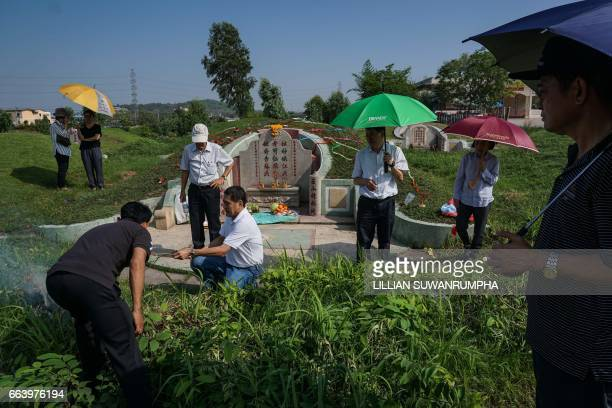 Members of a ThaiChinese family gather around the tomb of their ancestors and burn paper goods ahead of Qingming Festival or Tomb Sweeping Day in a...