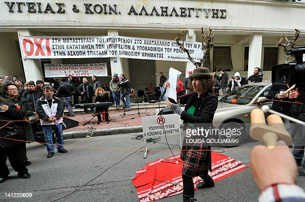 Members of a theatrical group stage a happening outside the Ministry of Health during a protest against the cuts in the social health system and...