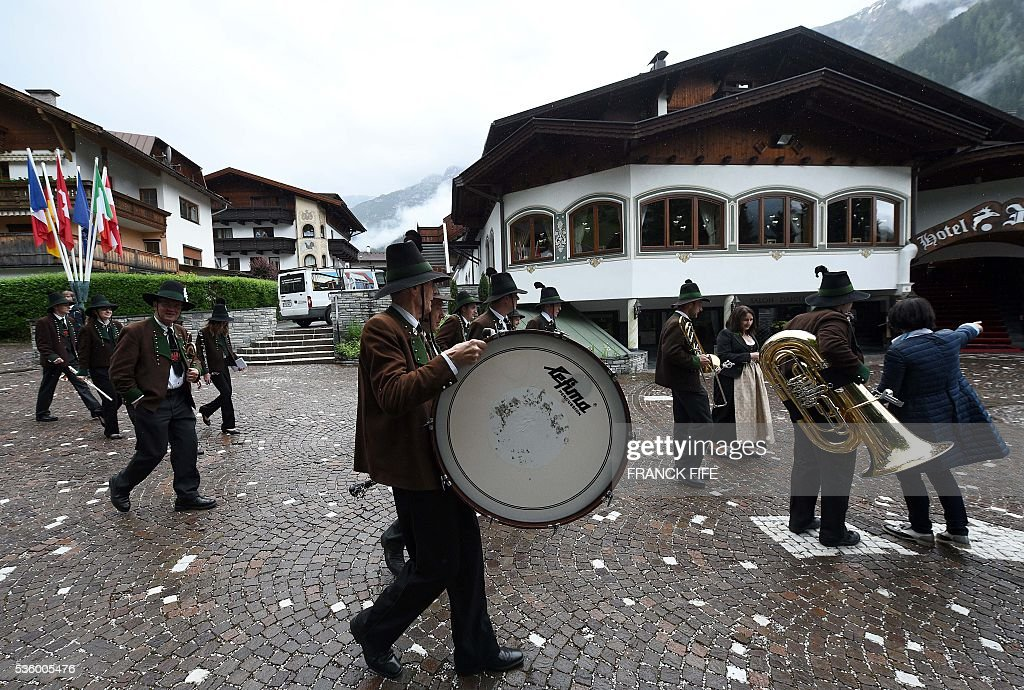 Members of a traditional music band walk past the hotel of the French national football team in Neustift im Stubaital near Innsbruck, Austria, on May 31, 2016, where the team stays for a traning camp as part of preparations for the upcoming Euro 2016 European football championships. / AFP / FRANCK