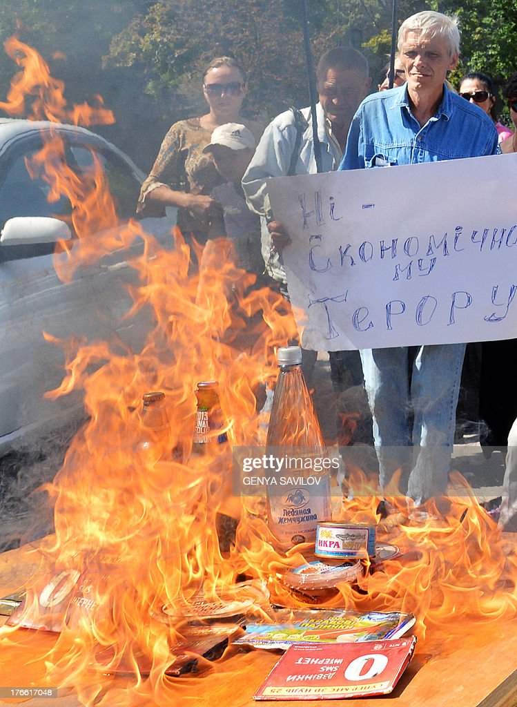 Members of a Ukrainian NGO burn goods produced in Russia during their protest in front of the Russia Embassy in Kiev on August 16, 2013. Ukraine is experiencing difficulties with its exports to Russia, the prime minister Mykola Azarov acknowledged on Thursday, amid growing tensions with Moscow over a Kremlin-led Customs Union. Placard read No economic terrorism.