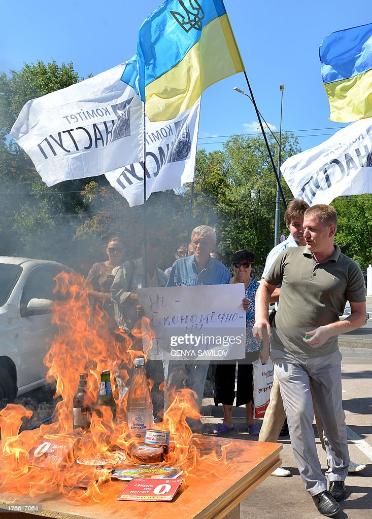 Members of a Ukrainian NGO burn goods produced in Russia during their protest in front of the Russia Embassy in Kiev on August 16, 2013. Ukraine is experiencing difficulties with its exports to Russia, the prime minister Mykola Azarov acknowledged on Thursday, amid growing tensions with Moscow over a Kremlin-led Customs Union. Placard reads No economic terrorism.