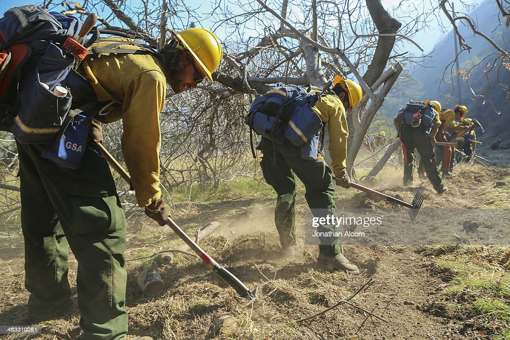 Members of a U.S. Forest Service clear brush at the Colby Fire on a hillside above Highway 39 on January 17, 2014 in Azusa, California. Three men have been arrested and charged with starting the fire that has now destroyed 1,700 acres of land and several homes around Glendora and Azusa in the San Gabriel Valley near Angeles National Forest, prompting officials to order evacuations for houses near the fire.