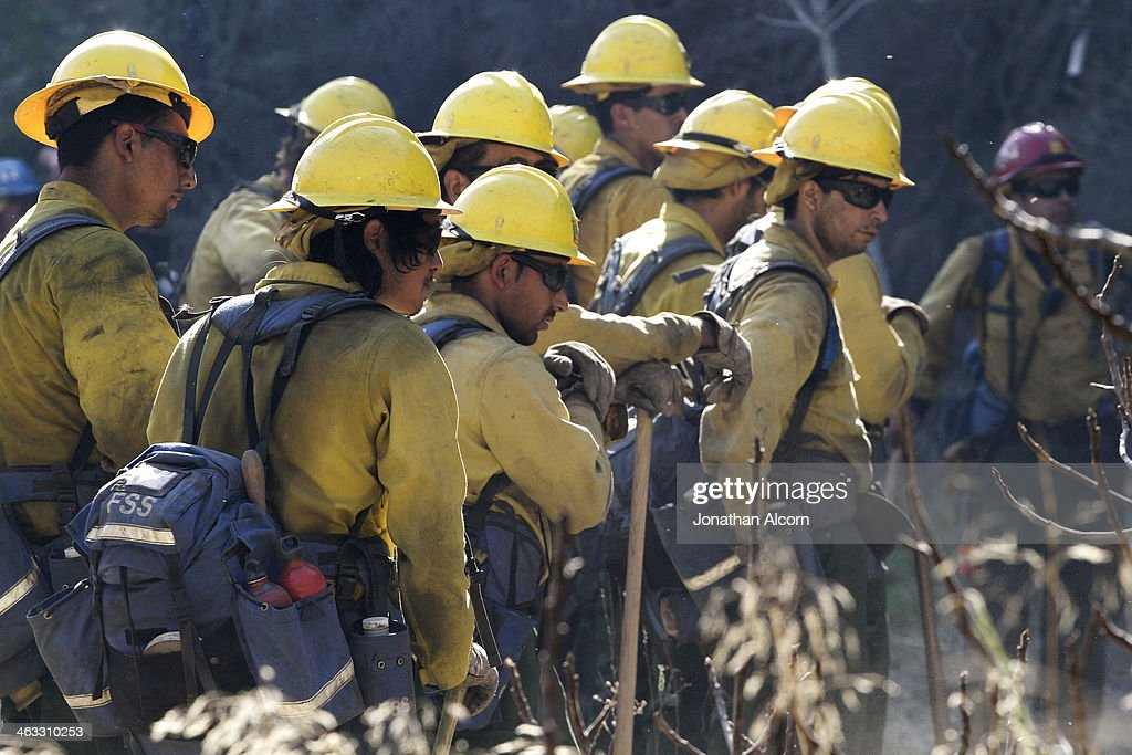 Members of a U.S. Forest Service hand crew take a break from clearing fire break lines at the Colby Fire on a hillside above Highway 39 on January 17, 2014 in Azusa, California. Three men have been arrested and charged with starting the fire that has now destroyed 1,700 acres of land and several homes around Glendora and Azusa in the San Gabriel Valley near Angeles National Forest, prompting officials to order evacuations for houses near the fire.