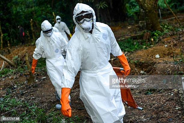 Members of a volunteer medical team wear special uniforms for the burial of 7 people sterilized after dying due to the Ebola virus in Kptema...