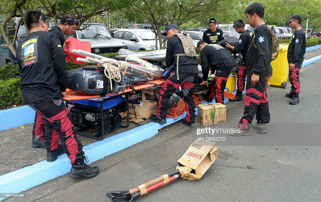Members of a volunteer rescue team from a mining company prepare their equipment at a military Base in Manila on November 12, 2013, before boarding a military cargo plane that will take them to the central coastal city of Tacloban which bore the brunt of Super Typhoon Haiyan when it swept through the central Philippines this weekend. The UN launched an appeal for a third of a billion dollars on November 12 as US and British warships steamed towards the typhoon-ravaged Philippines where well over 10,000 people are feared dead. AFP PHOTO / Jay DIRECTO