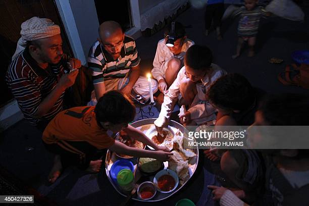 Members of a Yemeni family eat dinner on candle light in Sanaa late on June 10 2014 Yemen suffered a total blackout after gunmen in the eastern...
