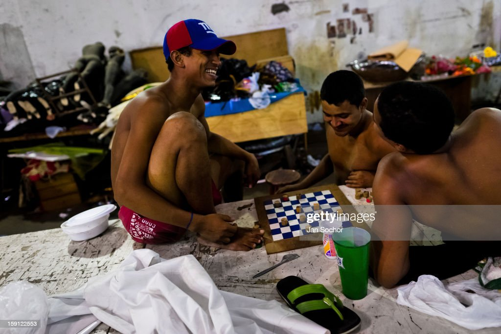 Members of Acadêmicos da Rocinha samba school play checkers inside the workshop in Rio de Janeiro, Brazil, 14 February 2012. The carnival preparations start early in July or August, some 7-8 months before the main samba schools parade at the sambodrome. Samba schools hire teams of professional designers and artists who, according to the original theme selected by the school directors and then featured by the school during the parade, create allegorical floats, costumes, sculptures, music, choreography and the entire school show. However, the most of the everyday work in the carnival hangars is performed by unknown but fully dedicated samba schools members.
