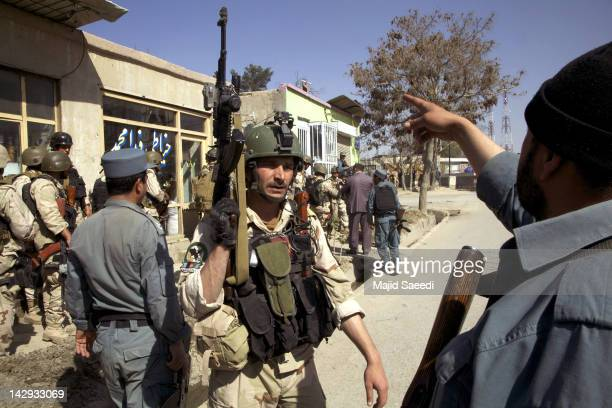 Members of Afghan security force take postion at the site of a gun battle after Taliban militants launched a series of coordinated attacks across the...