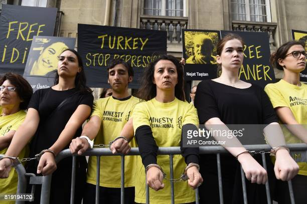Members of Amnesty International stand with their hands handcuffed as they stage a protest outside of the Turkish embassy in Paris on July 20 2017...