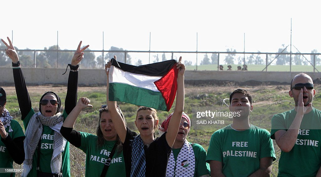 Members of an 87-strong delegation of mostly French and Egyptian pro-Palestinian activists, flash the V-sign as they protest against Israel during their visit in support of Palestinian farmers next to the security fence standing on the Gaza border with Israel, east of Gaza city on December 31, 2012. The mission 'Welcome to Palestine' aims to denounce the Israeli blockade of the Palestinian territory that was imposed in June 2006. AFP PHOTO/ SAID KHATIB