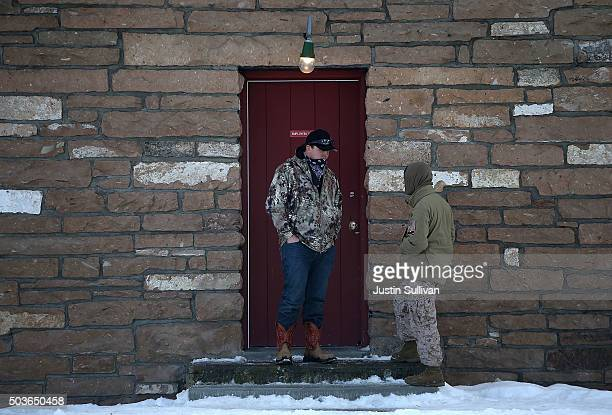 Members of an antigovernment militia stand in front of a building at the Malheur National Wildlife Refuge Headquarters on January 6 2016 near Burns...