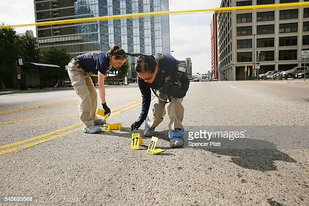 Members of an FBI evidence response team search an area that is still an active crime scene in downtown Dallas following the deaths of five police...