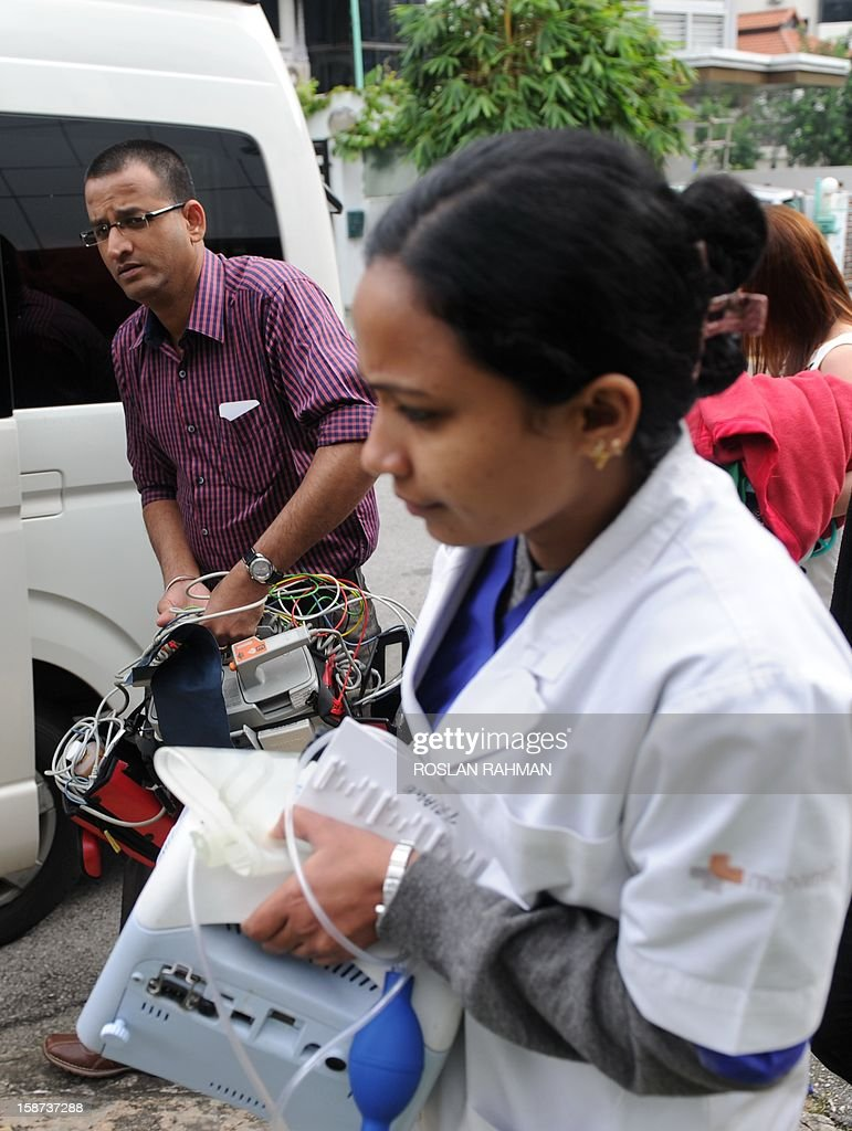 Members of an Indian medical team leave the Mount Elizabeth Hospital to board an embassy van in Singapore on December 27, 2012. An Indian student who was left fighting for her life after being brutally gang raped on a bus in New Delhi arrived on December 27 in Singapore for treatment at a leading hospital. AFP PHOTO / ROSLAN RAHMAN