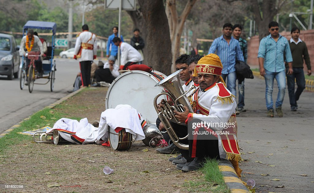 Members of an Indian wedding band wait on a road divider in New Delhi on February 17, 2013.