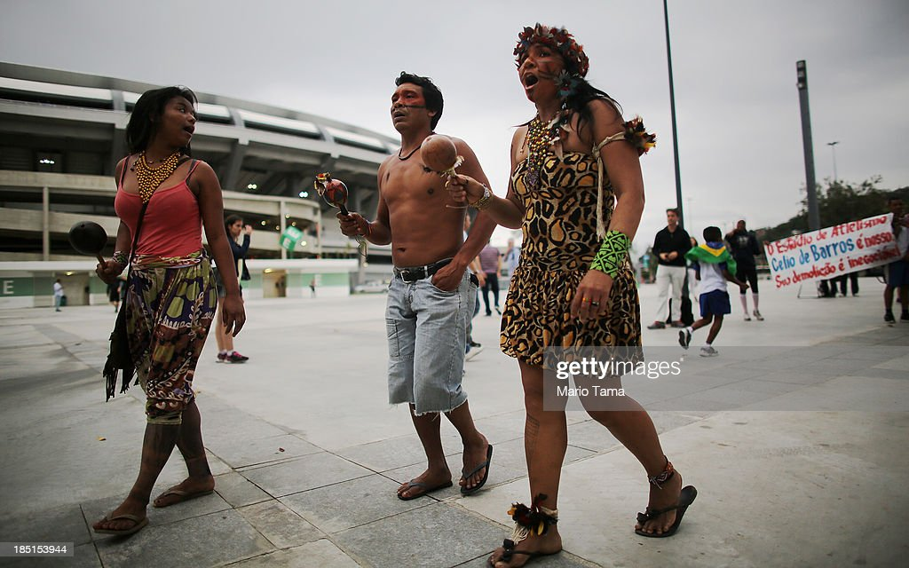 Members of an indigenous community walk to the Aldeia Maracana building they are occupying next to Maracana Stadium (TOP L), the site of the 2014 World Cup final, while giving a tour to visitors on October 17, 2013 in Rio de Janeiro, Brazil. The fading Aldeia Maracana used to house the Museum of Indian Culture before deteriorating and becoming occupied by squatting indigenous members in 2006. The building was slated for destruction ahead of the 2014 World Cup and the community was forcibly evicted in March. However, the community has managed to return and thus far have successfully battled to save the structure, which they hope to convert into an indigenous university. Indigenous groups throughout Brazil are battling the Brazilian government over land rights and other issues.