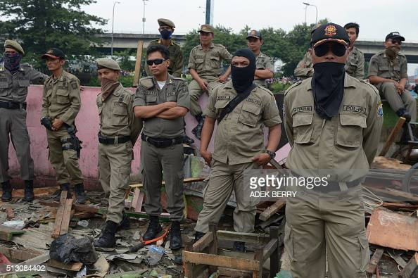 Members of an Indonesian civil service police unit watch as workers destroy houses at a redlight area known as Kalijodo in Jakarta on February 29...
