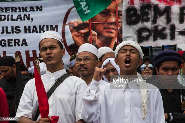 Members of an Indonesian Islamic group demonstrate in front of a sign illustrating Jakarta Governor Basuki Tjahaja Purnama better known as Ahok...