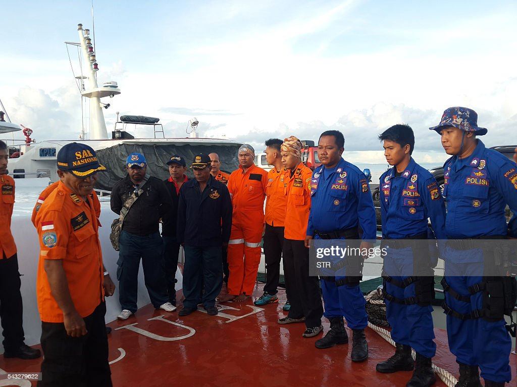 Members of an Indonesian search and rescue team have a briefing prior to a search and rescue operation in Biak on June 27, 2016. Twelve people are missing after a boat capsized in stormy weather off Indonesia's easternmost province of Papua, an official said on June 27. / AFP / STR