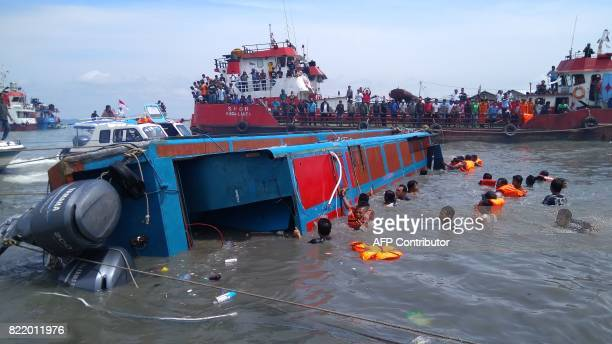 Members of an Indonesian search and rescue team try to help passengers from a capsized boat in Tarakan on July 25 2017 At least eight people...
