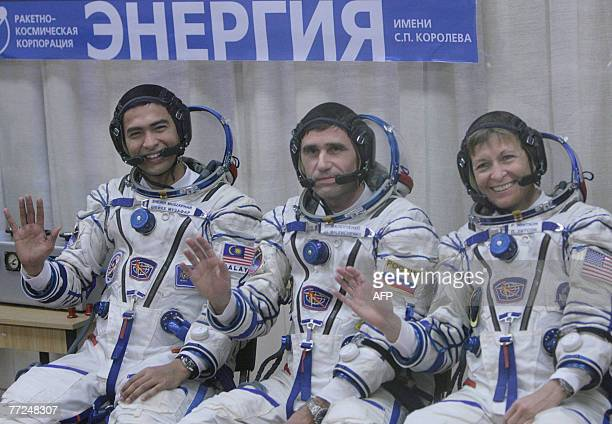 Members of an international space crew Sheikh Muszaphar Shukor of Malaysia Yury Malenchenko of Russia and US Peggy Whitson wave during a farewell...
