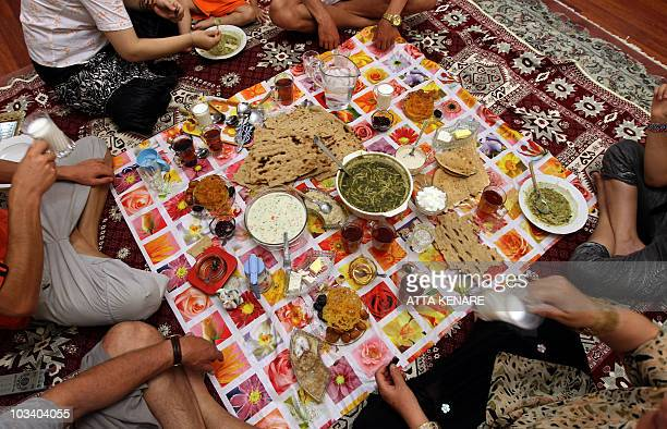 Members of an Iranian family attend on August 16 2010 at their home in Tehran an iftar the evening meal to break the daily fast observed by Muslims...