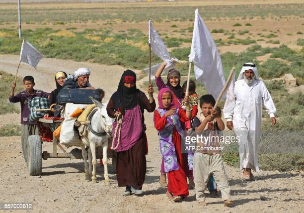 Members of an Iraqi family displaced from the outskirts of Islamic State group stronghold Hawija raise white flags while travelling with a donkeycart...