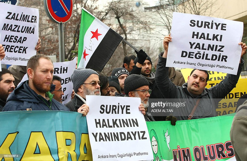 Members of an Islamic rights group hold banners that read 'We are with Syrian people' as they stage a protest against Iran for its support to the Syrian regime, outside the Iranian embassy in Ankara, on February 23, 2013.