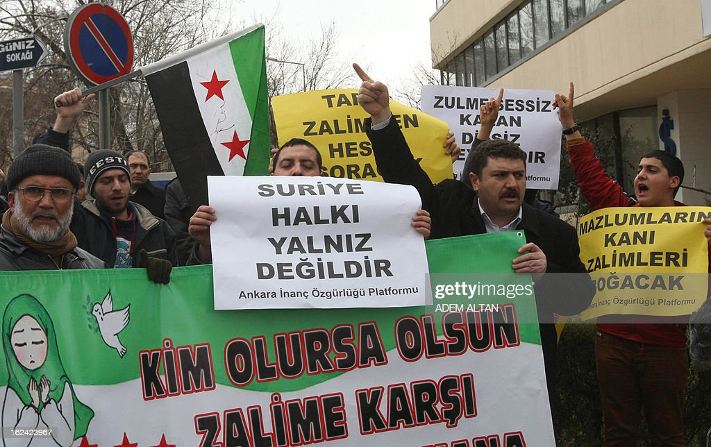 Members of an Islamic rights group hold banners that read 'We are with Syrian people' as they stage a protest against Iran for its support to the Syrian regime, outside the Iranian embassy in Ankara, February 23, 2013.