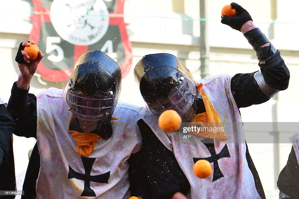 Members of an orange batlle team throw oranges during the traditional 'battle of the oranges' held during the carnival in Ivrea, near Turin, on February 10, 2013. During the event which marks the people's rebellion against tyrannical lords who ruled the town in the Middle Ages, revellers parading on floats represent guards of the tyrant, while those on foot the townsfolk.