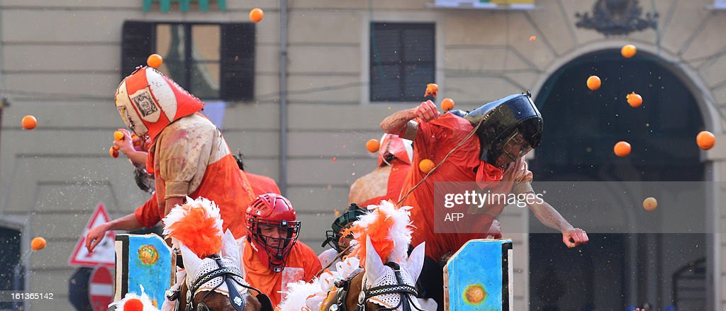 Members of an orange battle team throw oranges during the traditional 'battle of the oranges' held during the carnival in Ivrea, near Turin, on February 10, 2013. During the event which marks the people's rebellion against tyrannical lords who ruled the town in the Middle Ages, revellers parading on floats represent guards of the tyrant, while those on foot the townsfolk.
