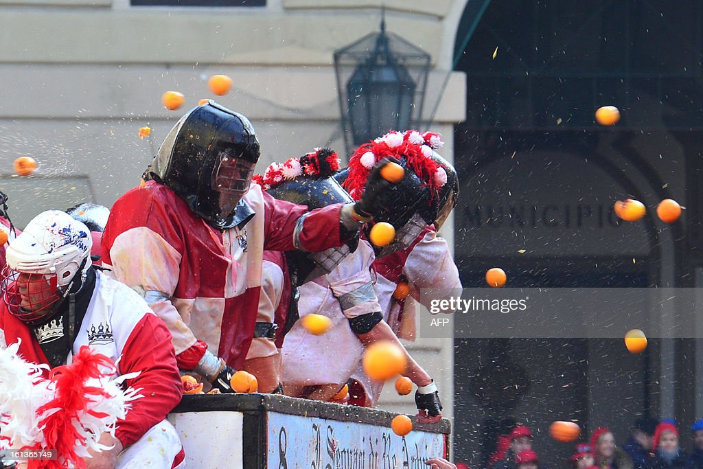 Members of an orange battle team throw oranges during the traditional 'battle of the oranges' held during the carnival in Ivrea, near Turin, on February 10, 2013. During the event which marks the people's rebellion against tyrannical lords who ruled the town in the Middle Ages, revellers parading on floats represent guards of the tyrant, while those on foot the townsfolk. AFP PHOTO / GIUSEPPE CACACE