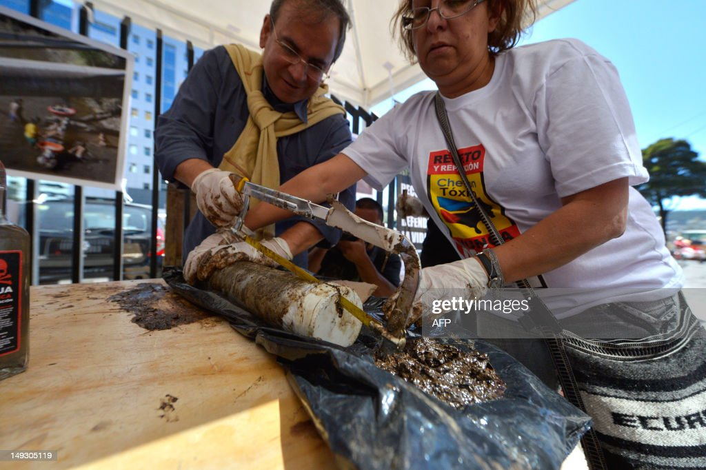 Members of an organization of indigenous people affected by US oil company Chevron prepare samples of earth and water contaminated with oil during a rally in front of the National Court of Justice in Quito, on July 26, 2012. The plaintiffs against Chevron will undertake more legal actions against Chevron overseas to be compensated wuith around USD 19,022 million for enviromental damage, one of the defendants' lawyers said Thursday. AFP PHOTO/RODRIGO BUENDIA