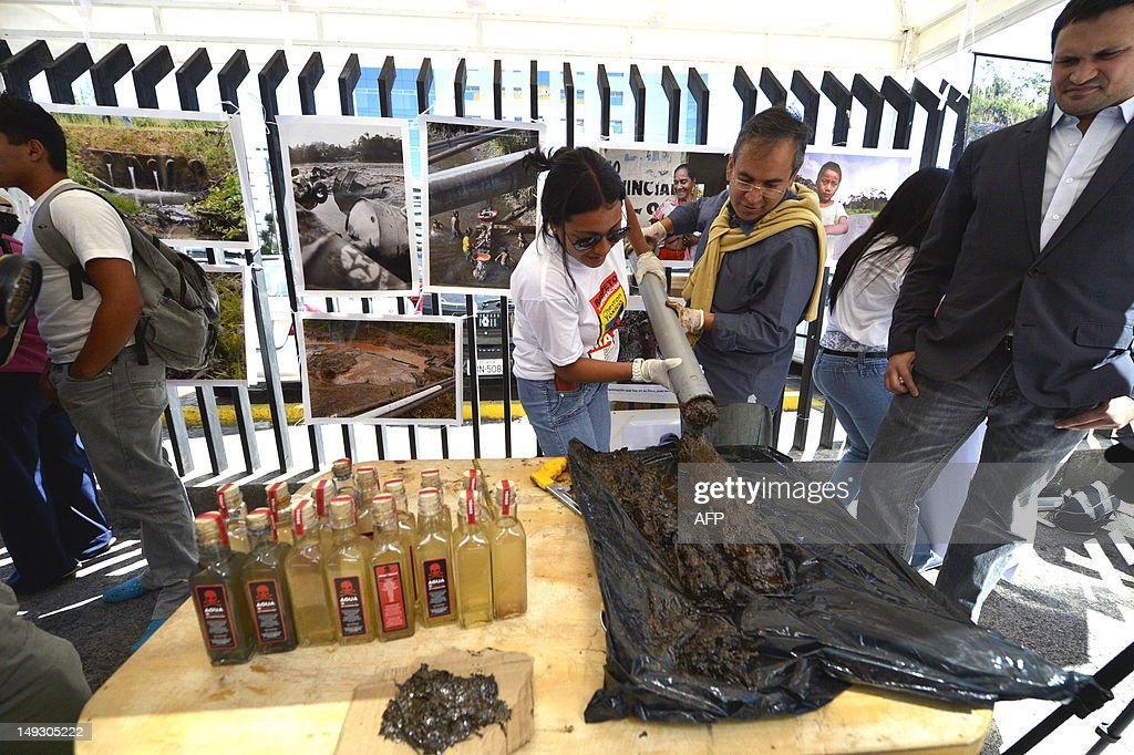 Members of an organization of indigenous people affected by US oil company Chevron prepare samples of earth and water contaminated with oil during a rally in front of the National Court of Justice in Quito, on July 26, 2012. The plaintiffs against Chevron will undertake more legal actions against Chevron overseas to be compensated wuith around USD 19,022 million for enviromental damage, one of the defendants' lawyers said Thursday.