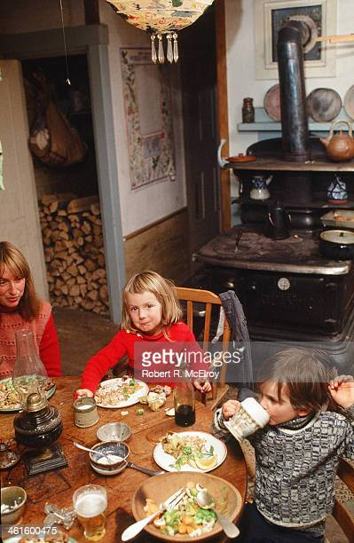 Members of an unidentified family two children and a woman eat dinner at a wooden table New York January 2 1978 In the background is a woodburning...