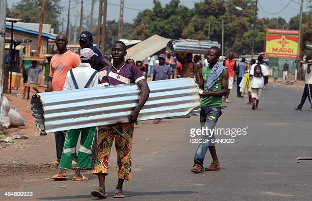 Members of antiBalaka militia carry corrugated iron roofs looted from houses belonging to Muslims on January 24 2014 at P12 district in the north of...