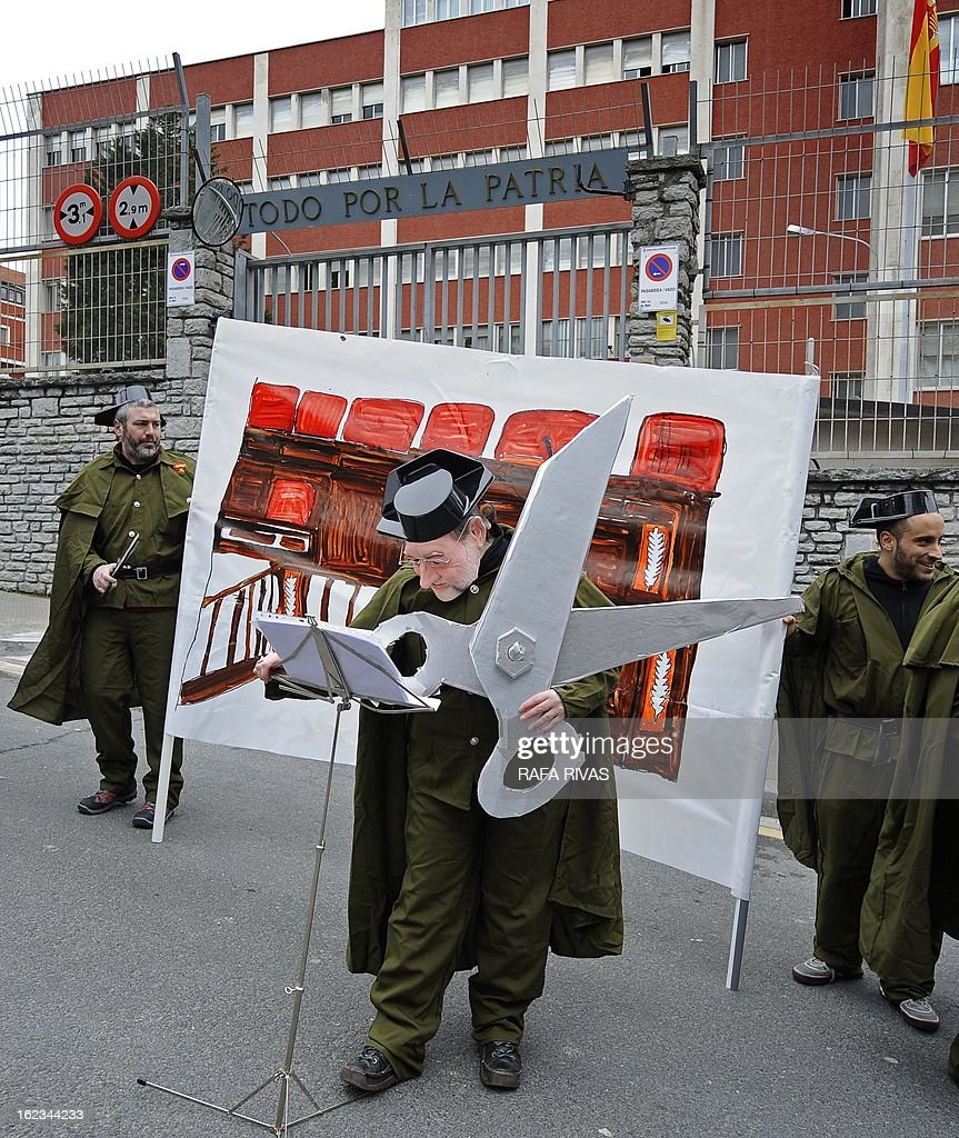 Members of anti-military group Kakitzat wear Guardia Civil uniforms and a mask depecting Spain's Prime Minister Mariano Rajoy during a protest against government's cuts and the military expense to mark the 32nd anniversary of the attempted coup d'etat in Spain, on February 22, 2013, in the Northern Spanish Basque city of Bilbao.