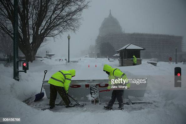 Members of Architect of the Capitol clears snow on a driveway of the US Capitol January 23 2016 in Washington DC Heavy snow continued to fall in the...