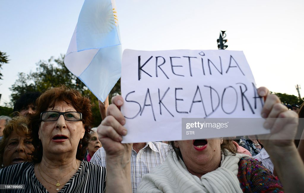 Members of Argentinian rural organizations shout slogans during a protest against a decree issued by President Cristina Fernandez de Kirchner to expropiate the Rural Society grounds and give it back to the state, on December 27, 2012 at the Rural Society grounds in Buenos Aires. Sign reads 'Cretinous looter' (deliberately misspelled with a K for Kirchner). AFP PHOTO