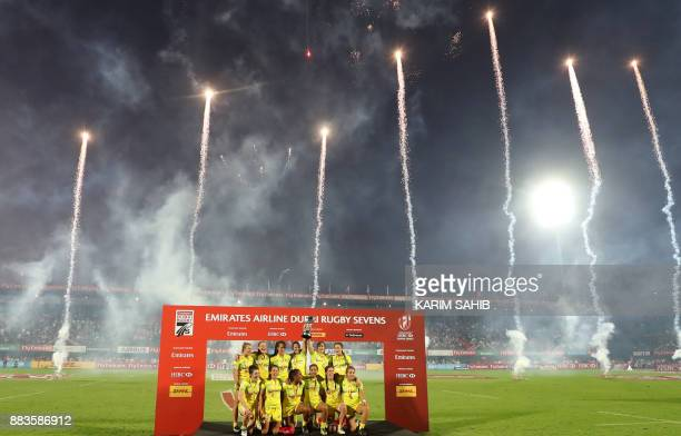 Members of Australia's women's national rugby sevens team lift the trophy as they celebrate their victory after defeating the United States in the...