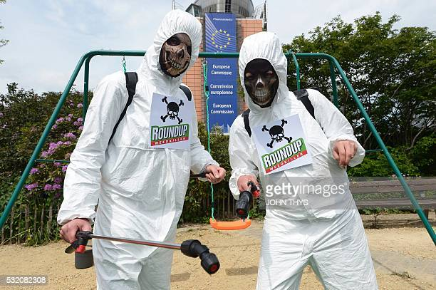 Members of Avaaz civic organization dress as cropsprayers on May 18 2016 at the Schuman roundabout in Brussels in protest at the European...