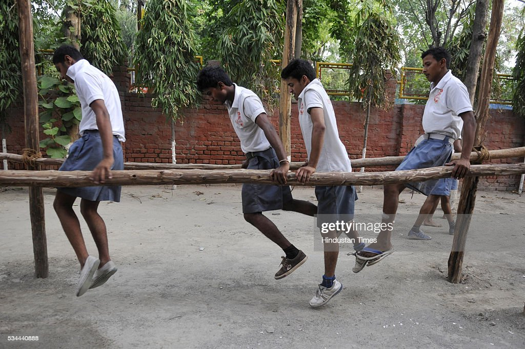 Members of Bajrang Dal doing Army style training during self defense training camp at Saraswati Shishu Mandir, an RSS-run school on May 26, 2016 in Noida, India. Nearly 400 members from 16 districts of Uttar Pradesh have gathered at the Saraswati Shishu Mandir in Noida for the training session. The training module includes martial arts, hurdle jumping, airgun firing, rope climbing and use of swords and sticks during a combat situation. The arms training camp of Hindu Right Wing oraganisation in communally sensitive Ayodhya has triggered furore earlier this week, prompting Police to arrest the camp organizer Mahesh Mishra .