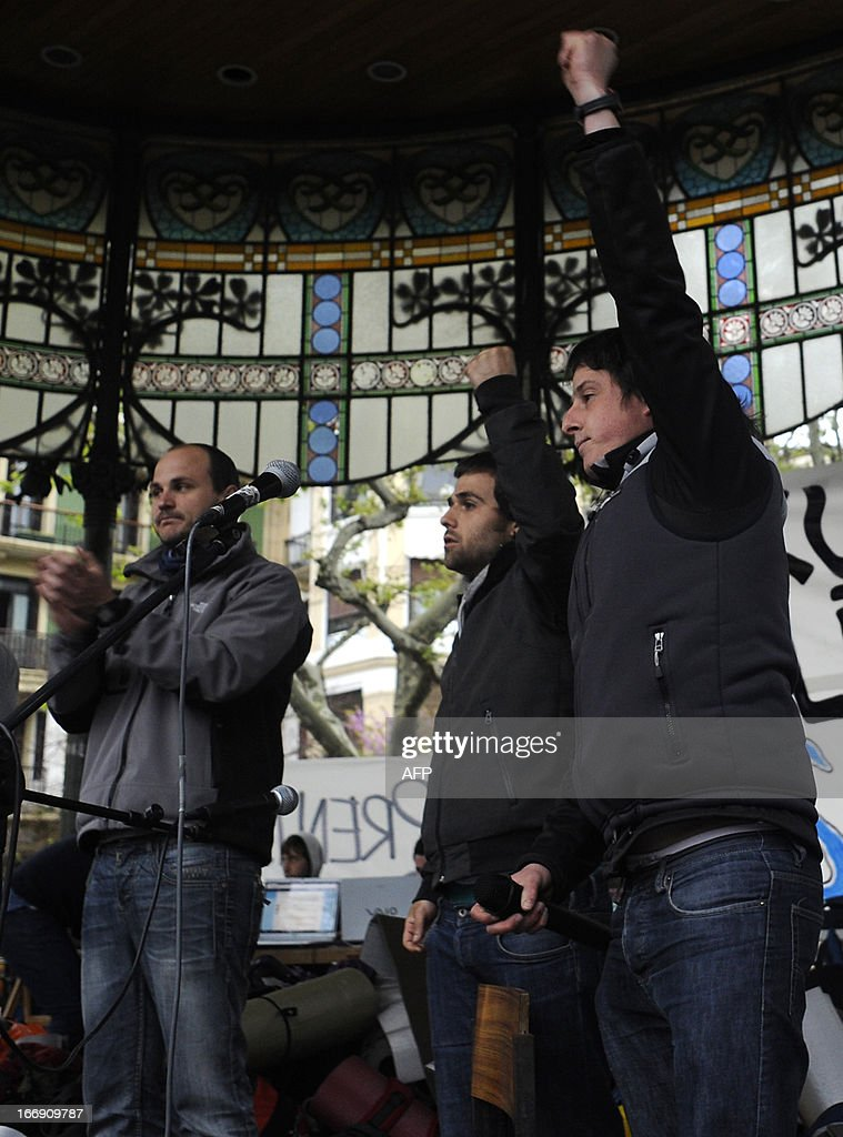 Members of Basque pro-independence youth organization SEGI Oier Lorente, Egoi Alberdi and Aitor Olaizola raise their fist after delivering a speech in the northern Spanish Basque city of San Sebastian on April 18, 2013. Hundreds of people remain gathered in San Sebastian, to prevent the incarceration of eight members of SEGI sentenced to six years in prison by the Supreme Court. The Spanish Court issued arrest warrants on April 16 against Mikel Arretxe, Imanol Vicente, Naikari Otaegi, Egoi Alberdi, Aitor Olaizola, Adur Fernandez, Oier Lorente y Ekaitz Ezkerra for membership in an organized armed group. AFP PHOTO / ANDER GILLENEA