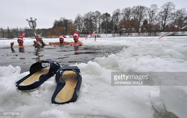 Members of Berlin's ice swimming club 'Berliner Seehunde' take a dip in the Orankesee lake during their traditional Christmas ice swimming session in...