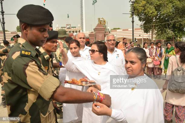 Members of Brahma Kumaries tying rakhis on the wrists of BSF jawans on the occasion of Raksha Bandhan festival at Attar Border near on August 7 2017...