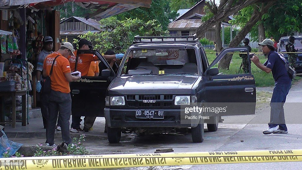 Members of Brimob police surround the car at the crime scene where crossfire between police with paramilitary groups in Sanginora took place . The shootout resulted into killing of two unidentified men. Police suspects the existence of supporters and sympathizers of the group Santoso in the Blue Mountains , Poso Pesisir.
