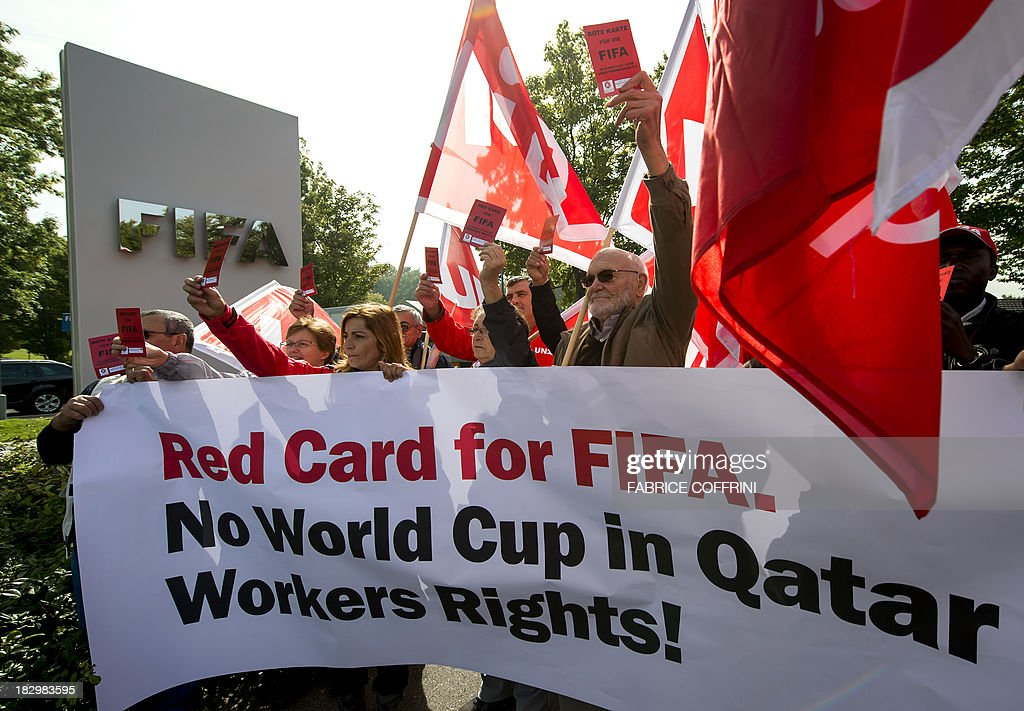 Members of Building and Wood Workers' International (BWI) and Swiss Unia unions hold a red cards reading 'A red card for FIFA, no World Cup without labour rights' and a banner reading 'No World Cup in Qatar Workers Rights!' during a demonstration outside the headquarters of the world's football governing body FIFA in Zurich on October 3, 2013. The protest came amid a report by Britain's Guardian saying that dozens of Nepalese construction workers treated like 'slaves' have died working at World Cup projects in Qatar in recent weeks. In 2010 Qatar won the right to host the 2022 FIFA World Cup. The FIFA executive committee is meeting in Zurich to discuss the tournament's timetable after calls for it to be staged in winter because of the desert emirate's scorching summer.