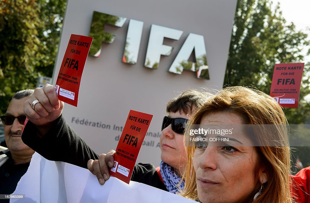 Members of Building and Wood Workers' International (BWI) and Swiss Unia unions hold red cards reading 'A red card for FIFA, no World Cup without labour rights' during a demonstration outside the headquarters of the world's football governing body FIFA in Zurich on October 3, 2013. The protest came amid a report by Britain's Guardian saying that dozens of Nepalese construction workers treated like 'slaves' have died working at World Cup projects in Qatar in recent weeks. In 2010 Qatar won the right to host the 2022 FIFA World Cup. The FIFA executive committee is meeting in Zurich to discuss the tournament's timetable after calls for it to be staged in winter because of the desert emirate's scorching summer.